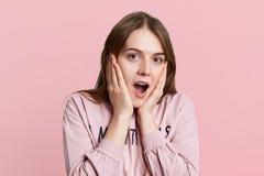 Headshot szokująca piękna kobieta utrzymuje ręki na policzkach, spojrzenia w terrorze przy kamerą, jest ubranym przypadkowego pul Obrazy Stock