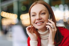 Headshot van aantrekkelijke jonge vrouw met blije gelaatsuitdrukking, besprekingen via celtelefoon, heeft bruin haar, gelukkig om stock foto's