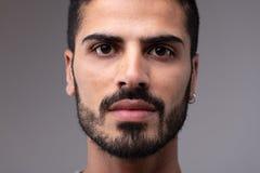 Headshot van de jonge gebaarde mens met het earing stock fotografie
