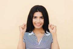 Headshot van gelukkig donkerbruin vrouwelijk model klemt vuisten dicht, hoopt voor goed iets, heeft brede glimlach met witte perf stock foto's