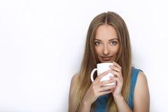 Headshot van jonge aanbiddelijke speelse blondevrouw met leuke glimlach in de blouse van de kobaltkleur het stellen met grote zui Royalty-vrije Stock Afbeelding