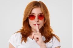 Headshot van vrij jong wijfje met ernstige uitdrukking maakt in het geheim stilteteken, bekijkt camera, vertelt privé informatie  stock fotografie