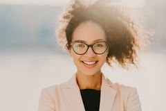 Headshot van vrolijke krullende vrouw met positieve uitdrukking, draagt bril, wit elegant jasje, bekijkt straightly camera, stock fotografie