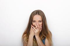 Headshot von jungen entzückenden Blondinen bedeckt ihren Mund auf weißem Hintergrund Lizenzfreies Stockfoto