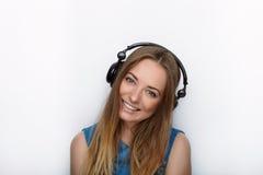 Headshot von jungen entzückenden Blondinen mit dem netten Lächeln, das große schwarze Berufsüberwachungskopfhörer gegen weißes St Lizenzfreies Stockfoto