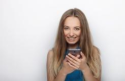 Headshot von jungen entzückenden Blondinen mit nettem Lächeln auf dem weißen Hintergrund, der auf ihrem Smartphone simst Lizenzfreie Stockfotos