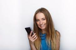 Headshot von jungen entzückenden Blondinen mit nettem Lächeln auf dem weißen Hintergrund, der auf ihrem Smartphone simst Lizenzfreies Stockbild