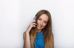 Headshot von jungen entzückenden Blondinen mit nettem Lächeln auf dem weißen Hintergrund, der auf ihrem Smartphone simst Lizenzfreies Stockfoto
