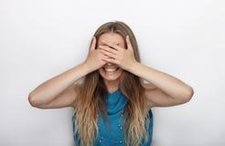 Headshot von jungen entzückenden Blondinen mit nettem Lächeln auf weißem Hintergrund bedeckt ihr Gesicht mit Palmen Stockfotos