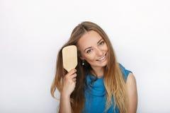 Headshot von jungen entzückenden Blondinen mit nettem Lächeln mit Kamm bürsten in der Hand ihr Haar auf weißem Hintergrund Stockbild