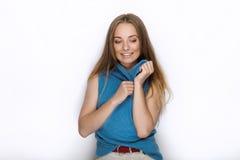 Headshot von jungen entzückenden spielerischen Blondinen mit nettem Lächeln in der Kobaltfarbbluse, die auf weißem Hintergrund au Stockfoto