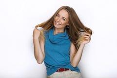 Headshot von jungen entzückenden spielerischen Blondinen mit nettem Lächeln in der Kobaltfarbbluse, die auf weißem Hintergrund au Lizenzfreie Stockbilder