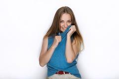 Headshot von jungen entzückenden spielerischen Blondinen mit nettem Lächeln in der Kobaltfarbbluse, die auf weißem Hintergrund au Stockfotografie