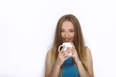 Headshot von jungen entzückenden spielerischen Blondinen mit nettem Lächeln in der Kobaltfarbbluse, die mit großem Reinweißbecher Lizenzfreies Stockbild