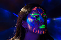 Headshot woman wearing awesome glow in dark facial. Paint, blue based with other neon colors and obscure abstract background, facing camera stock photo