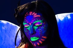 Headshot woman wearing awesome glow in dark facial. Paint, blue based with other neon colors and obscure abstract background, facing camera stock images