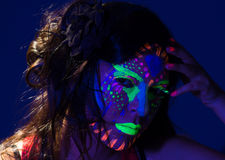 Headshot woman wearing awesome glow in dark facial. Paint, blue based with other neon colors and obscure abstract background, facing camera royalty free stock photos