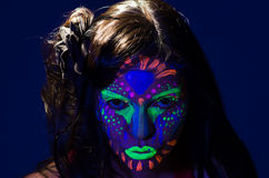 Headshot woman wearing awesome glow in dark facial. Paint, blue based with other neon colors and obscure abstract background, facing camera stock image