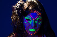 Headshot woman wearing awesome glow in dark facial. Paint, blue based with other neon colors and obscure abstract background, facing camera royalty free stock photo