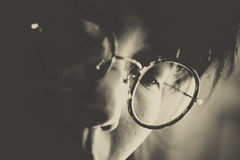 Headshot of women with round glasses looking downward concentrat. Headshot of woman with round glasses looking downward concentrate on somethings in sepia color Royalty Free Stock Image