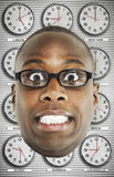Headshot of worried man wearing glasses with various time zone clocks in background Royalty Free Stock Photos