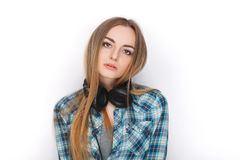 Headshot of a young adorable blonde woman in blue plaid shirt enjoying listening music to big professional dj headphones. Headshot of a young adorable blonde Royalty Free Stock Photo