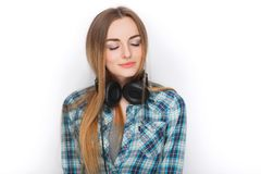 Headshot of a young adorable blonde woman in blue plaid shirt enjoying listening music to big professional dj headphones. Headshot of a young adorable blonde Royalty Free Stock Photos