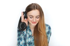 Headshot of a young adorable blonde woman in blue plaid shirt enjoying listening music to big professional dj headphones. Stock Images