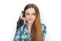 Headshot of a young adorable blonde woman in blue plaid shirt enjoying listening music to big professional dj headphones. Royalty Free Stock Images