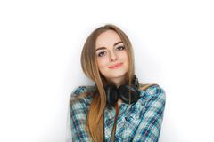 Headshot of a young adorable blonde woman in blue plaid shirt enjoying listening music to big professional dj headphones. Royalty Free Stock Photography