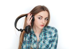 Headshot of a young adorable blonde woman in blue plaid shirt enjoying listening music to big professional dj headphones. Headshot of a young adorable blonde Royalty Free Stock Photography