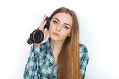 Headshot of a young adorable blonde woman in blue plaid shirt enjoying listening music to big professional dj headphones. Headshot of a young adorable blonde Stock Photography