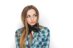 Headshot of a young adorable blonde woman in blue plaid shirt enjoying listening music to big professional dj headphones. Headshot of a young adorable blonde Stock Photo