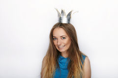 Headshot of young adorable blonde woman with cute smile in hand made princess crown on white background Stock Photos