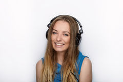 Headshot of young adorable blonde woman with cute smile wearing big black professional monitoring headphones against white studio Stock Photos
