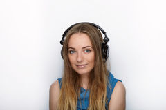 Headshot of young adorable blonde woman with cute smile wearing big black professional monitoring headphones against white studio Royalty Free Stock Images