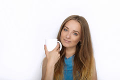 Headshot of young adorable playful blonde woman with cute smile in cobalt color blouse posing with big pure white mug on white bac Royalty Free Stock Image