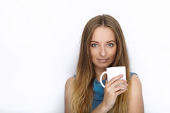 Headshot of young adorable playful blonde woman with cute smile in cobalt color blouse posing with big pure white mug on white bac Stock Image