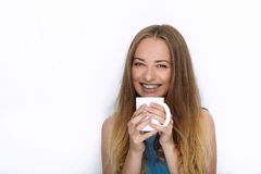 Headshot of young adorable playful blonde woman with cute smile in cobalt color blouse posing with big pure white mug on white bac Royalty Free Stock Photo
