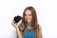 Headshot of young adorable playful blonde woman with cute smile in cobalt color blouse posing with black dslr camera on white back Stock Photos