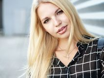 Headshot of young beautiful excited woman with gorgeous natural lips, blue and brown eyes in black blouse on urban metal strips ba Royalty Free Stock Photos