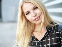 Headshot of young beautiful excited woman with gorgeous natural lips, blue and brown eyes in black blouse on urban metal strips ba Royalty Free Stock Images