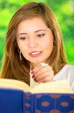 Headshot young brunette model reading book, captivated facial expression and garden background Royalty Free Stock Image