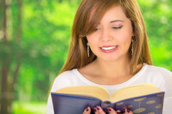 Headshot young brunette model reading book, captivated facial expression and garden background Stock Photos