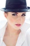 Headshot of young business woman wearing man's shirt, hat Royalty Free Stock Photo