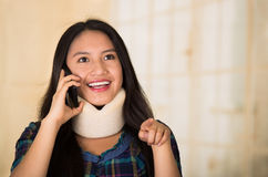 Headshot young hispanic woman posing wearing neck brace, smiling happily while talking on phone, injury concept.  royalty free stock photos