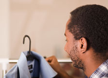 Headshot young man from behind, standing in front of clothing rack looking at blue shirt, fashion concept Stock Photos