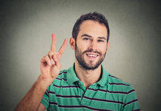 Headshot young man, handsome student holding up peace victory, two sign Stock Photography