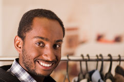 Headshot young man smiling to camera, standing in front of clothing rack, fashion concept Royalty Free Stock Image