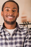 Headshot young man smiling to camera, standing in front of clothing rack, fashion concept Stock Photos